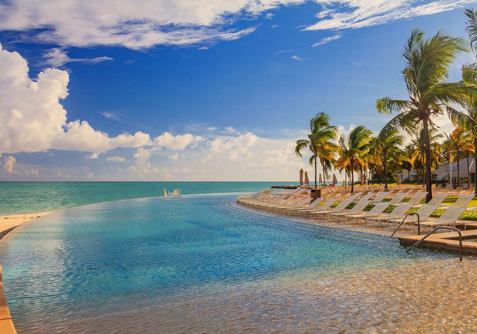 Pool  chairs by the turquoise water of the Caribbean sea and a pool on a tropical beach in Freeport, Bahamas